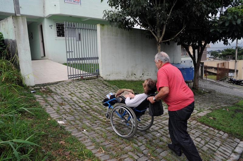 Um micro-ônibus que pega a pessoa em casa, leva para consultas de saúde e entrega novamente o paciente na porta de casa tem facilitado muito a vida de pessoas com deficiência.<br />-Na imagem,  Clotilde Maria Wosniak e Luiz Rodriguez.<br />Curitiba, 30/03/2015<br />Foto: Everson Bressan/SMCS