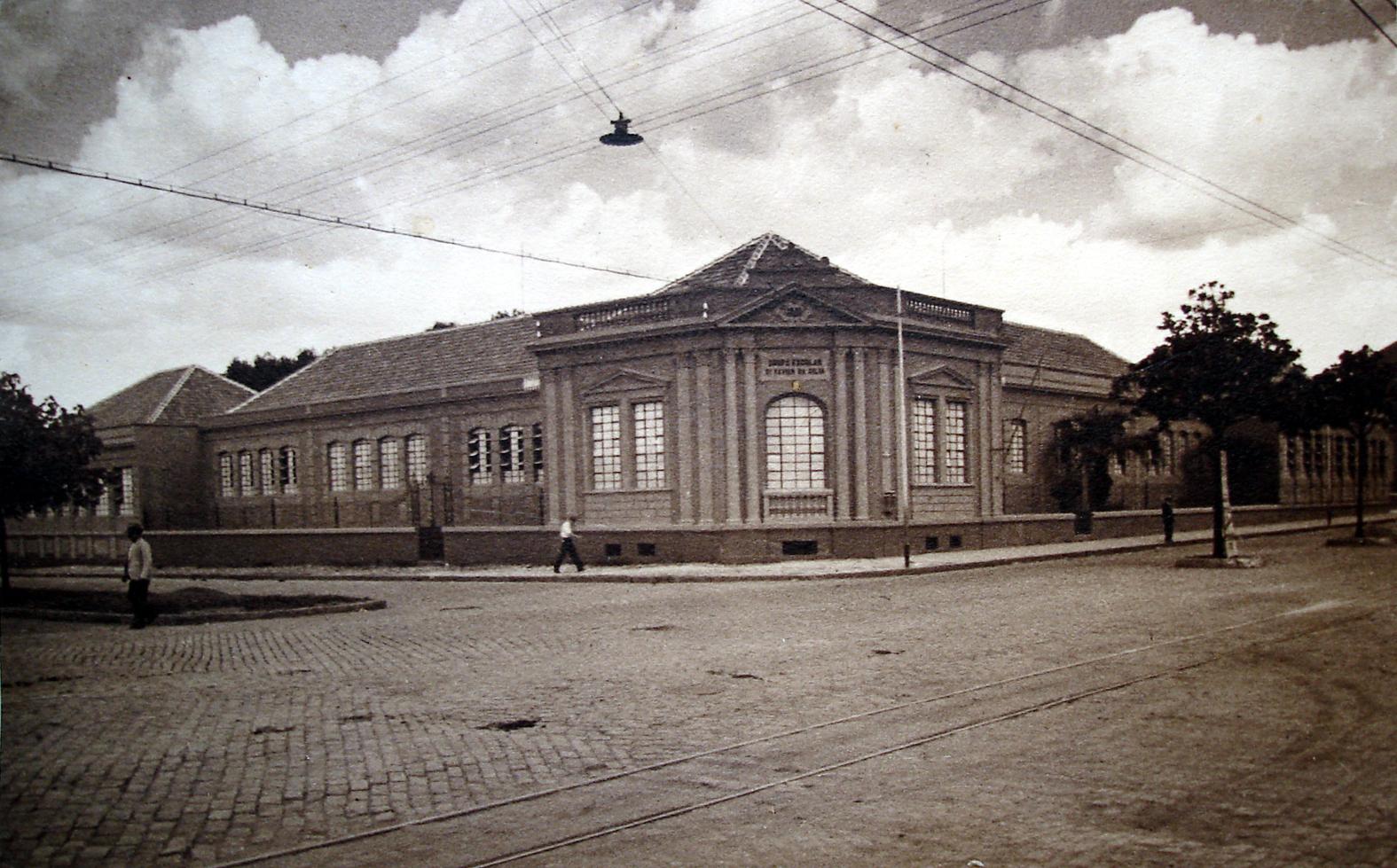 O Grupo Escolar Dr. Xavier da Silva, na década de 1910. Em primeiro plano, a Avenida São José (atual Marechal Floriano) já pavimentada e com os trilhos do bonde elétrico.