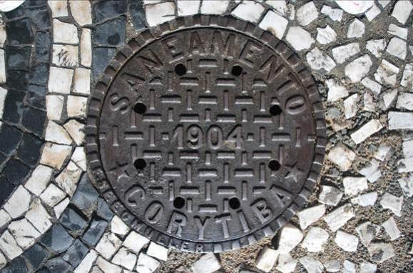 Tampa de inspeção da rede hidrossanitária, instalada em 1904, na Praça Osório. Algumas destas peças permaneceram no local até 2014, quando foram retiradas pela SANEPAR.
