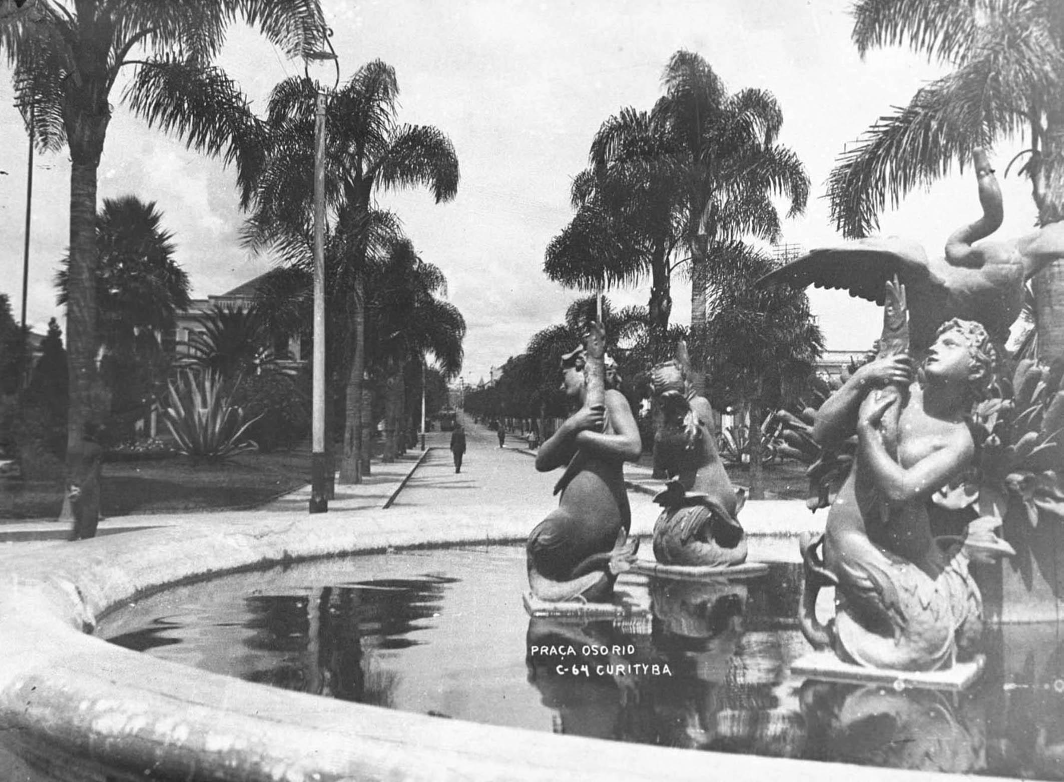 Cartão Postal mostrando, em primeiro plano, o repuxo circular e suas estátuas em bronze (do cisne e das sereias) da Praça Osório, que foram trazidas da Europa na metade da década de 1910.